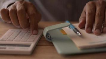 Close up hands of man calculating expenses on the desk at home. video