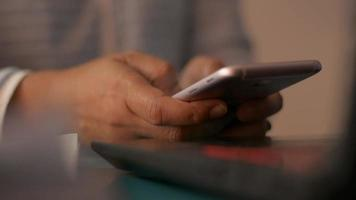 mujer manos mensaje de texto en el teléfono móvil inteligente en el escritorio de trabajo. video