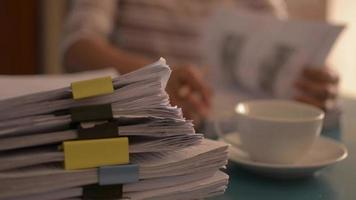Woman working with stack of documents on the desk at home. video