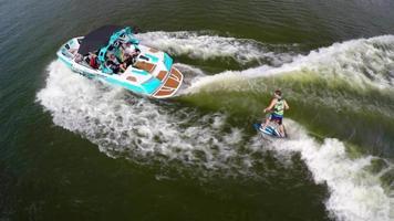 Toma aérea de un hombre de wakeboard surf detrás de un barco en un lago. video