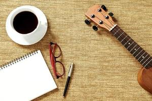 Top view of ukulele, notebook, pen, coffree cup and glasses photo