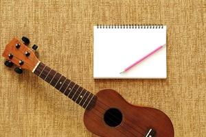 Top view of ukulele with notebook and pencil placed on brown fab photo
