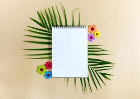 Notebook for mock up with green leaves of palm tree photo