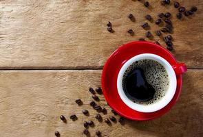 Red coffee cup on wooden table with coffee beads photo