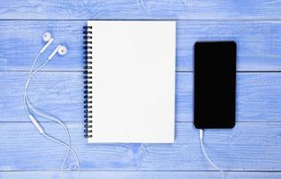 Los cuadernos, teléfonos y auriculares se colocan en el escritorio azul. foto