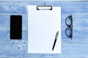 Clipboard with white sheet on wood background photo