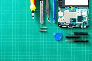 Partes de gadgets desmontados con destornilladores sobre mesa de madera foto