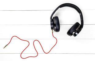 Carecen de auriculares y cable rojo aislar sobre fondo de mesa blanco de madera foto