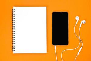 Vista superior de teléfonos inteligentes, auriculares sobre fondo naranja foto