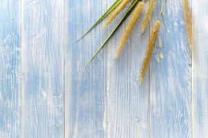 The grass flowers laid on a wooden floor photo