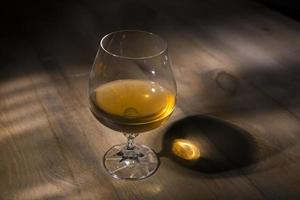 Glass of brandy or cognac on the wooden table photo