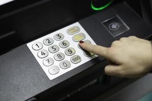 female hand dials a pin code at an ATM photo