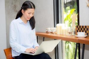 mujer asiática joven que trabaja en línea en la computadora portátil. foto