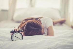 joven asiática apaga el despertador en buenos días. foto
