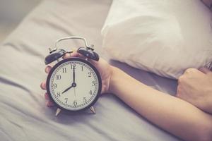 Primer plano las manos de la mujer apagan el despertador en buenos días. foto