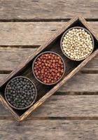Organic white red and black pepper corns in wood display photo