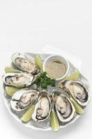 seis ostras frescas con rodajas de lima y salsa cítrica foto