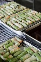 Muchos rollitos de primavera tailandeses frescos en la bandeja en la mesa de buffet en función foto