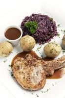 German-style grilled pork chop with bread dumplings and red cabbage traditional meal on white background photo