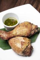 Muslos de pollo asado aperitivo con salsa picante de chile verde tailandés en la placa blanca. foto