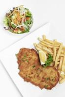 German-breaded pork schnitzel with french fries on white studio background photo