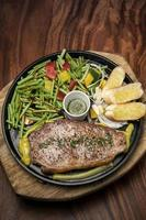 Organic tenderloin beef steak sizzler on hot plate meal platter with mixed vegetables and chimichurri sauce photo