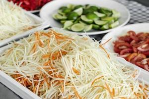 Thai Som Tam papaya salad ingredients at catering buffet preparation table station in Thailand photo