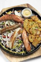 Mixed german traditional organic sausage and potato meal platter including Nurnberger, Lamb and Pork with salad and mustard photo