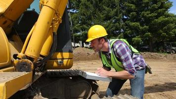 Worker inspecting excavation equipment video