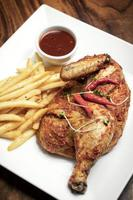 Spicy Portuguese piri piri half roast chicken with fries on plate in Lisbon restaurant photo