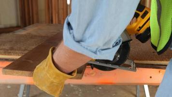 Primer plano de un trabajador de la construcción cortando madera contrachapada video