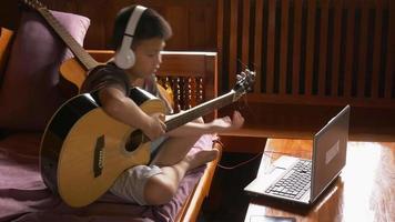 pojke lär sig spela gitarr online hemma video