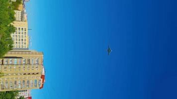 Plane flies over city. Airplane flying over building. vertical video