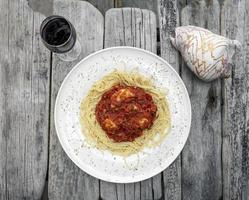 Bocconcini bolas de mozzarella en salsa de tomate ragú de verduras con espaguetis en rústica mesa de madera flotante con copa de vino tinto foto