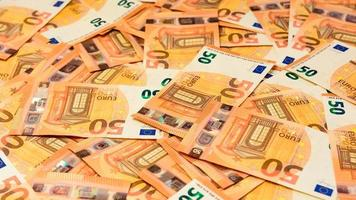 Banknotes in the denomination of 50 euros are scattered randomly photo