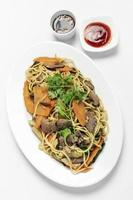 Traditional Khmer spicy beef stir fry with egg noodles and vegetables in Cambodia on white studio background photo