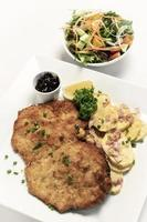 German breaded organic pork schnitzel with bacon fried potatoes cranberry sauce and salad on white studio background photo