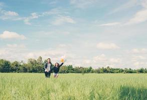 pareja joven, funcionamiento, y, tenencia, globo, en, el, pasto verde, debajo foto