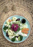 Rustic cottage salad with healthy mixed steamed and fresh vegetables on colorful plate outdoors in garden photo