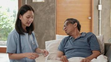 Female doctor checking health of  Asian elderly male patient at home. video