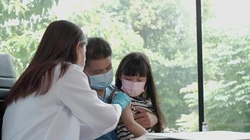 Female doctor vaccinating Asian girl At the pediatrics clinic. video