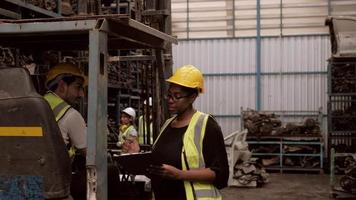 Black female engineer, male Caucasian forklift driver in warehouse. video