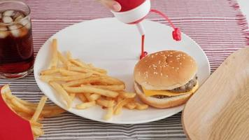 Ketchup in a white dish and junk foods. video
