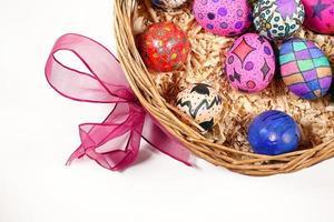 coloridos huevos de pascua en una canasta de madera foto
