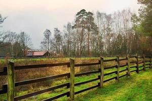 vallas de madera alrededor de granero y árboles foto