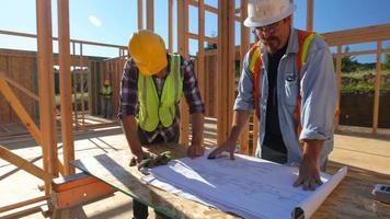 Construction workers looking over plans together video