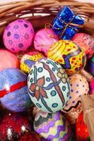 Coloridos huevos de pascua y caja de regalo en una canasta de madera foto