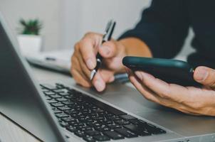 Cerrar mano empresario sosteniendo teléfono inteligente y usar computadora portátil foto