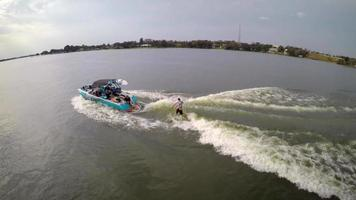 Aerial shot of a man wakeboard wake surfing behind a boat on a lake. video