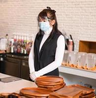 Coffee shop business owner wearing surgical mask. photo